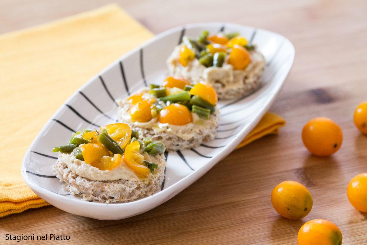 Bruschetta con hummus, fagiolini e pomodori gialli