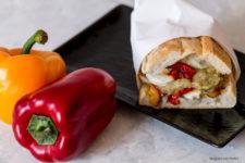 Panino con peperoni arrostiti, crema di melanzane e mozzarella stagioni nel piatto